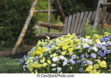 Swingset and Flowers - wooden swing and flowerbed in a...