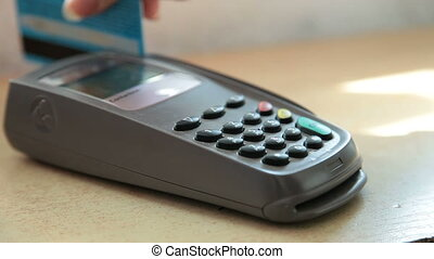 Female hand swiping a credit card through a credit card terminal