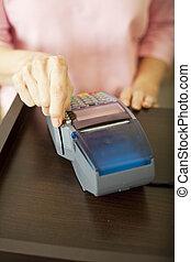 Swiping Debit Card - Closeup of a woman\'s had swiping a...