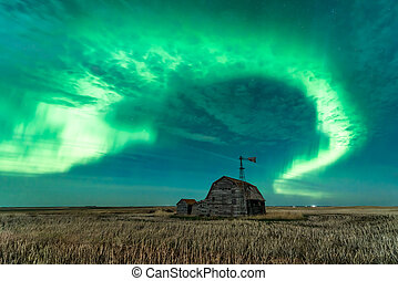 Swirl of bright Northern Lights over abandoned vintage barn, bins, windmill and stubble in Saskatchewan, Canada