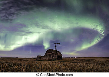 Swirl of bright Northern Lights over vintage barn and windmill in Saskatchewan, Canada