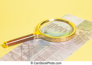 Swiss 1000 Franc banknotes under magnifying glass