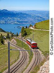 Swiss alpine cog railway train climbing up to the mount Rigi