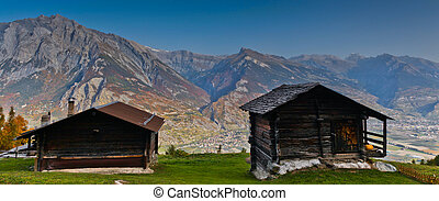 A couple of huts with Swiss Alps as background