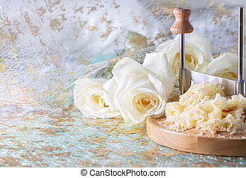 Swiss cheese Monk Head with crumbs on a wooden round surface and beautiful white roses. Blur background.