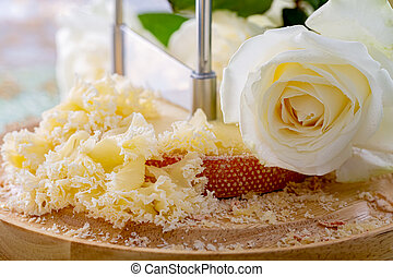 Swiss cheese with crumbs on a wooden round surface and beautiful white rose. Blurred background and bokeh. Soft focus.