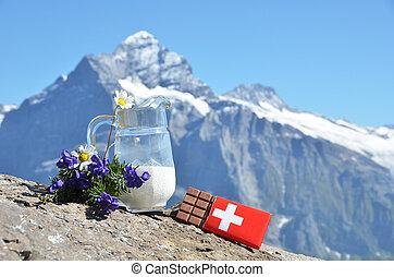 Swiss chocolate and jug of milk against mountain peak. Switzerland