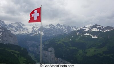 Swiss flag fluttering in the Alps
