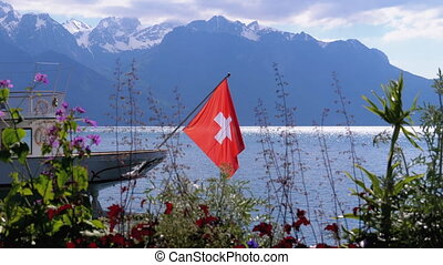 Swiss Flag on a Background of Alpine Mountains and Flowers...