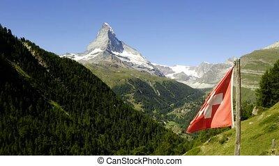 Swiss flag on mountain top in front of Matterhorn
