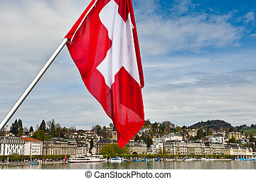 Swiss Flag on the Background of the Embankment of the River...