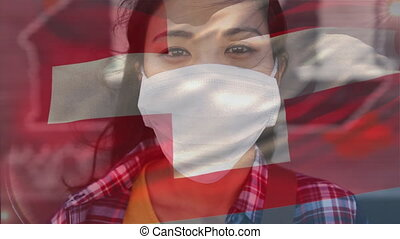 Animation of Swiss flag waving over Asian woman wearing a face mask, looking at the camera and smiling. Covid-19 coronavirus national health safety concept digital composite