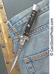 Switchblade knife on old blue jeans