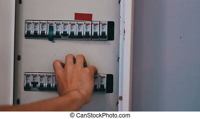 Switching Electric Breaker Box. Man hand turns on and off...