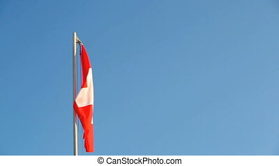 Switzerland flag in front of a blue sky