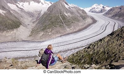 Hiker woman relaxing after trekking in Swiss Alps, Valais Canton, Switzerland, Europe. Woman looking Aletsch Glacier from Eggishorn summit with capped snow of Eiger, Monch and Jungfrau in summer.