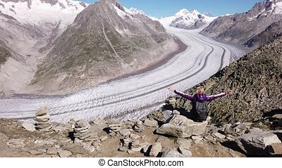 Hiking in Swiss Alps, Canton of Valais, Europe. Blonde carefree woman enjoying spectacular views of Aletsch Glacier from Eggishorn with panorama on capped snow of Eiger, Monch and Jungfrau in summer.