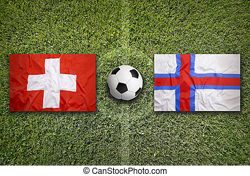Switzerland vs. Faroe islands flags on soccer field