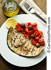 swordfish with tomatoes and lemon on wood