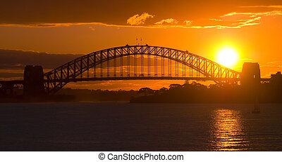 Sunsets behind Sydney Harbor ( Harbour ) Bridge - a deep golden orange sunset