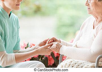 sygeplejerske, hånd ind hånd, i, disabled, elderly kvinde, på, den, wheelchair
