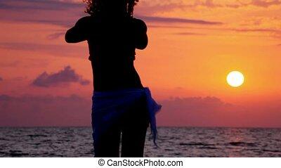 sylwetka, od, młoda kobieta, taniec, na, plaża, zachód...