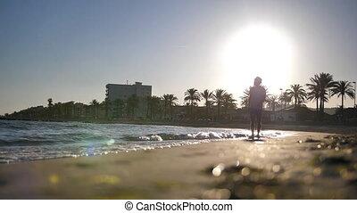 sylwetka, przechadzki, szorty, młody, zachód słońca, wzdłuż, kapelusz, plaża, podczas, człowiek