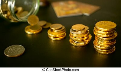 Symbol of investing, keeping money concept. Close-up still life with increasing columns of gold coins on black table