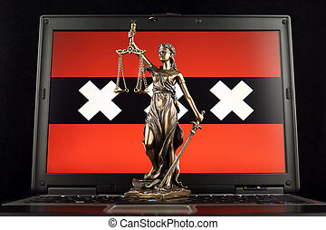 Symbol of law and justice with Amsterdam City Flag on laptop. Studio shot.