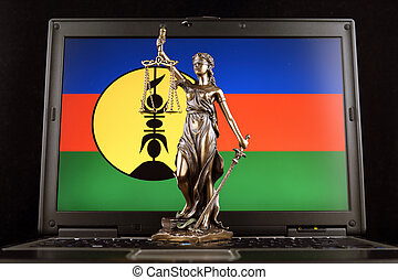 Symbol of law and justice with New Caledonia Flag on laptop. Studio shot.