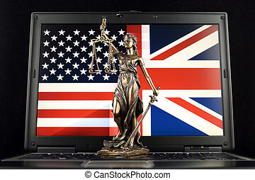 Symbol of law and justice with United States and United Kingdom Flag on laptop. Studio shot.