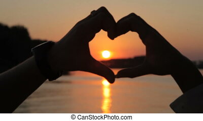 Symbol of love, heart from the hands of lovers at sunset
