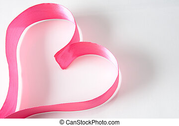 Symbol of love - Form of heart made up of pink ribbon over...