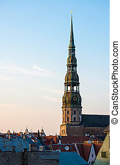 Symbol of Riga, old clock on medieval church tower of St. Peters among roofs ancient buildings with European architecture