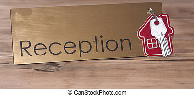 Symbol of the house with silver key on wooden reception desk