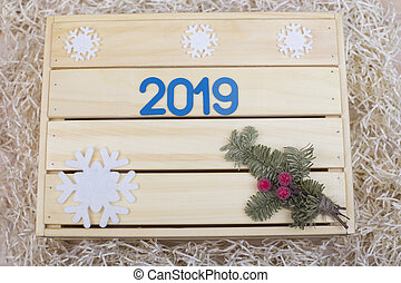 Symbol with and spruce twig on a wooden background with snowflakes
