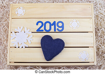 Symbol with number 2019 and a heart on a wooden background with snowflakes