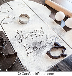 Symbolic image Easter cake with utensils on a dark wooden background.