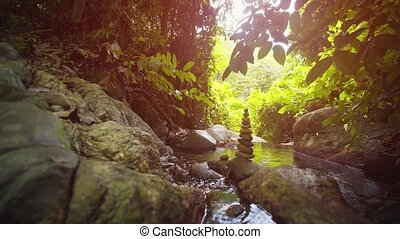 Ten rounded stones, precisely balanced and stacked into a symmetrical cairn, beside a peaceful, mountain stream in Thailand. Stock footage 4k
