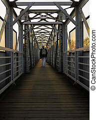 Symmetry view of footbridge over railway track with the man walking at sunset.