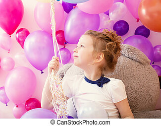 Sympathetic little girl holding bunch of balloons