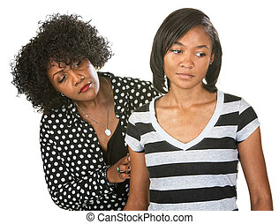 Sympathetic mother touching the arm of sad teenage daughter