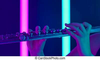 Symphony concert of classical music performed by a professional flutist. Female hands touch keys of the flute close up. Wind instrument against the background of bright purple neon lights. Slow motion.