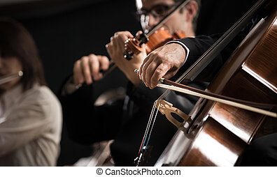 Symphony orchestra performing with cello player hand close-up.