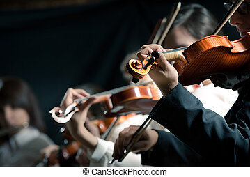 Symphony orchestra violinists performing on stage against dark background.
