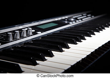 Synthesizer keyboard in shadow, music on black background