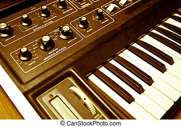 synthesizer with knobs and keys - A yellow hued shot of a...