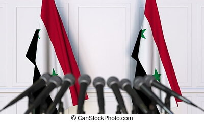 Syrian official press conference. Flags of Syria and...
