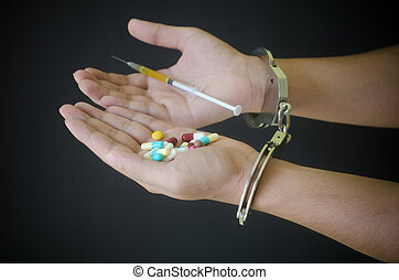 syringe and drug in hand and handcuffs - syringe and drug in...