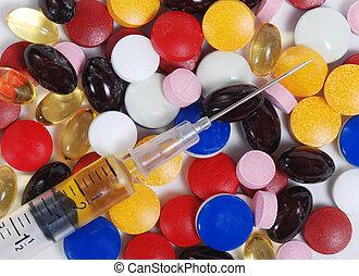 Syringe and medication - Syringe and variety of pills....